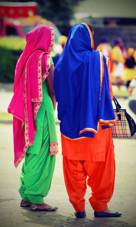 kameez: two women with multicolored clothing attending the event along the street of the city