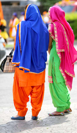 two women with multicolored clothing attending the event along the street of the city