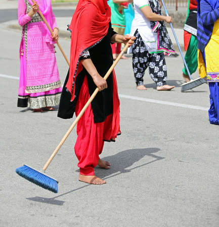 kameez: many barefoot women with colorful clothes sweep the paved road at the ceremony along the streets of the city Stock Photo