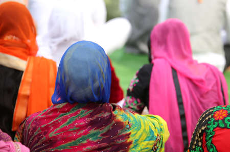 kameez: woman with a headscarf to cover her head during a gathering of people in the city