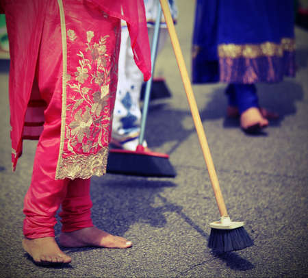 kameez: many barefoot women sweep the road during the celebration along the streets of the city Stock Photo