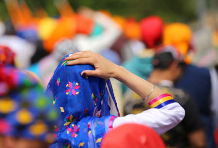 kurta: woman wearing blue veil headscarf during a gathering of people in the city