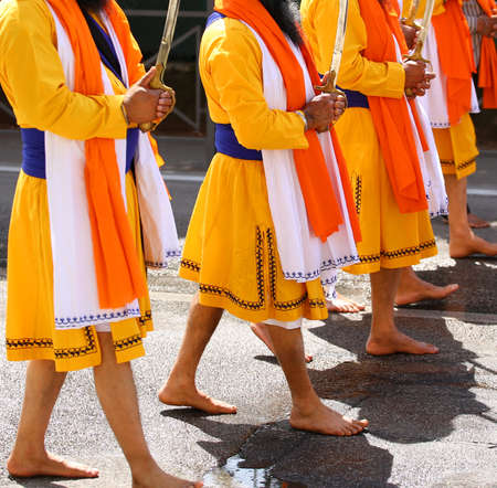 Sikh men walk barefoot through the streets of the city