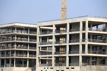 overbuilding: huge building under construction with reinforced concrete walls on the outskirts of the city