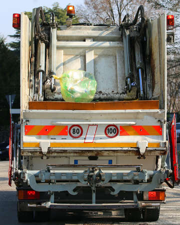 huge urban sanitation trucks during the collection of solid waste in the city and a big yellow bag of garbage Imagens