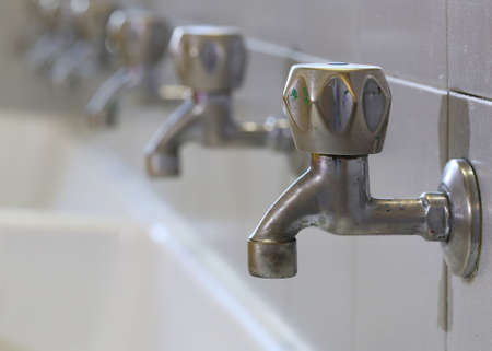 series of many dirty of colored paint stainless steel taps in a sink of a school for the infancy