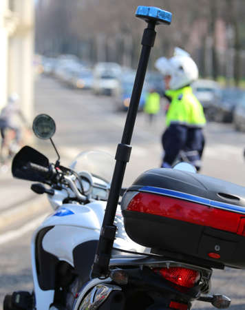 motorcycle police with flashing siren and a traffic officer on the street