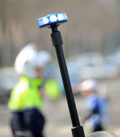 round flashing siren of motorcycle police and a traffic officer on the street