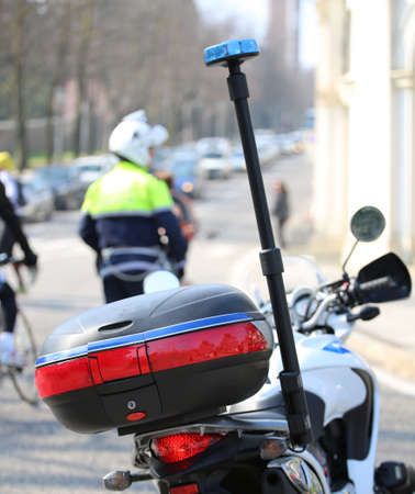motorcycle police with flashing siren and a traffic officer on the road Stock Photo