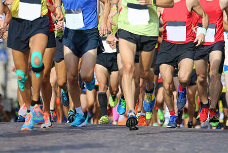 muscular legs of a large number of runners during sports race through the streets of the city