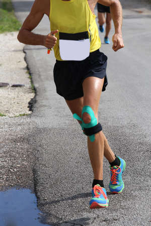 taping: athletic runner with elastic band at the knee running fast during the sporting event on the road