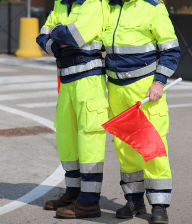 two men of the civil protection with garish uniform and the red flag to signal the danger in Italy