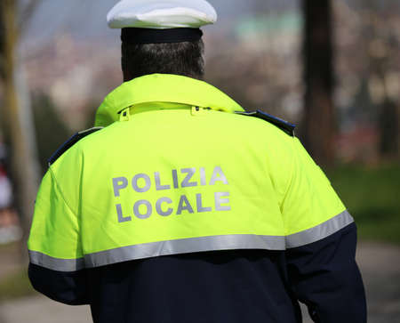 traffic warden: traffic cop with high visibility uniform and the words local police in italian during the patrolling and control in the city Stock Photo