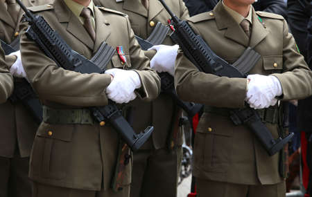 italian alpine troops: two men in full uniform Alpine Italian Mountain Troops during the military parade for the celebration of the Italian armed forces with rifle and white gloves Editorial