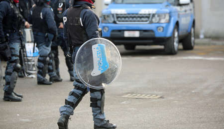 Vicenza, VI, Italy - January 28, 2017: armed escort of the Italian police during the transfer of football fans with bulletproof vest and defensive shield Editorial