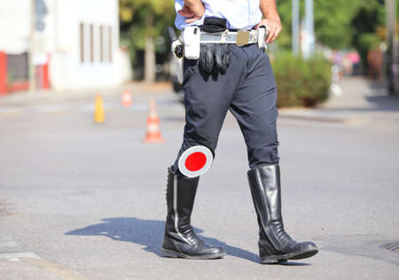 black boots and traffic pallet of a traffic policeman on the road
