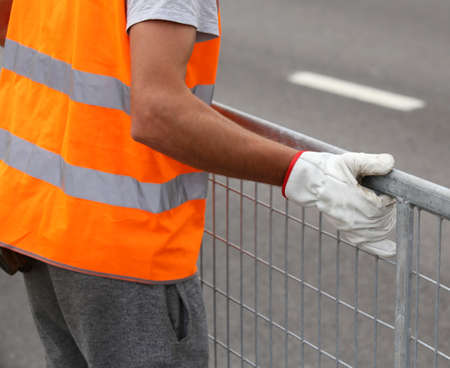 delimit: worker with orange high-visibility vest while moving the iron fences to delimit the space reserved for spectators