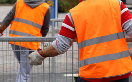 delimit: workers with orange high-visibility vest while moving the iron fences to delimit the space reserved for spectators during the event