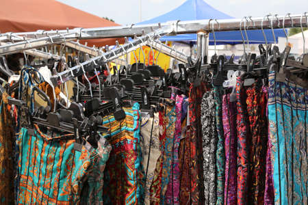 used clothes: stall in an outdoor market with lots of clothes hanging for sale