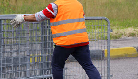 delimit: worker with orange high-visibility vest while moving the fences to delimit the space reserved for spectators Stock Photo