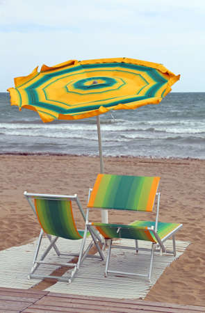 sunshade: rough sea and the beach with an umbrella in the wind with two deck chairs during a windy day in early summer Stock Photo