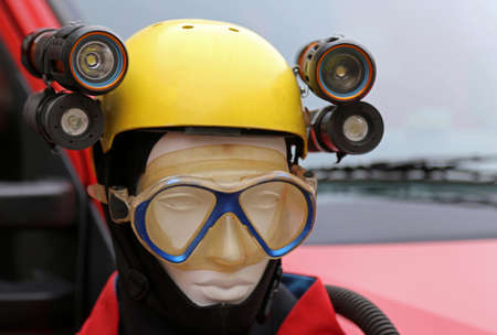 caving: professional equipment for lighting during emergencies and caving expeditions with a dummy is a yellow protective helmet