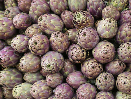 green background of ripe artichokes for sale in Southern Italy market Stock Photo