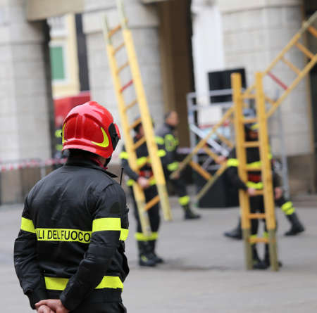 rungs: Italian firefighters with protective helmet during outdoor exercise with a long ladder with wooden rungs Stock Photo