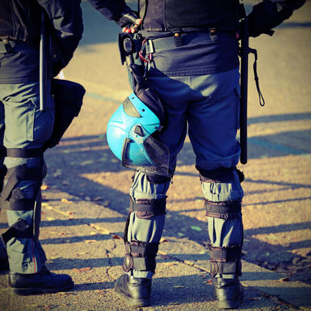 police in riot gear with protective helmet during the urban revolt of the protesters in the city Imagens