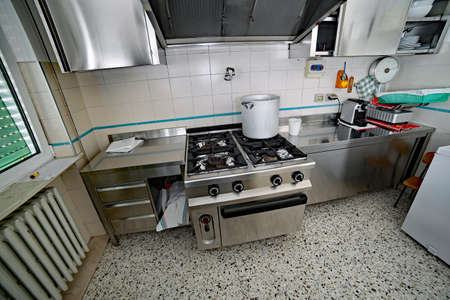 Industrial Kitchen With Steel Furniture And A Large Aluminum Pot On The Gas  Stove Photo