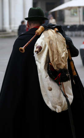 bagpipe: bagpiper with an old black cape and the bagpipes on the shoulders