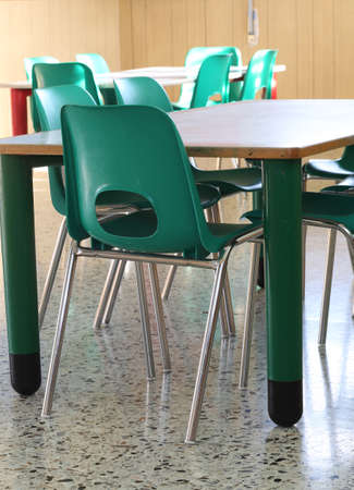 Inside the classroom of a school with green chairs and small tables Stock Photo