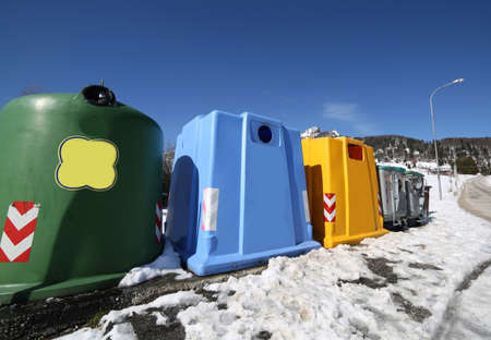 repurpose: many bins for the collection of waste in a mountain village in winter with snow