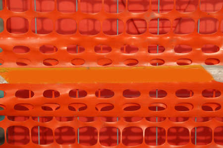 delimit: Plastic orange safety net to delimit the area of a road construction site in the city
