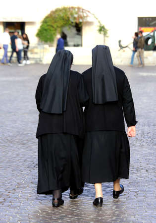 religious habit: two sisters with long blacks clothes they walk through the streets of European cities