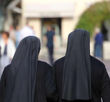 彼らは街を歩く長い黒服と姉妹