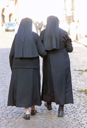 two sisters with black dresses and a veil to cover the hair walking in the european city