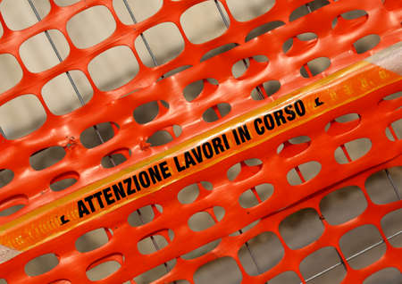 delimit: Plastic safety net to delimit the area of a road construction site with words ATTENZIONE LAVORI IN CORSO meaning CAUTION WORK IN PROGRESS in Italian Stock Photo