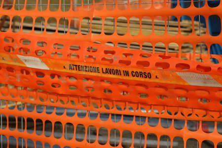 delimit: Plastic orange safety net to delimit the area of a road construction site with ITALIAN words meaning CAUTION WORK IN PROGRESS