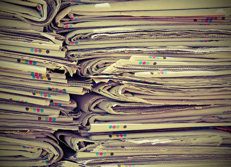 repurpose: piles of paper used and already read newspapers ready for the paper production processors used