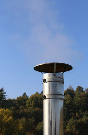 very cold: chimney steel with polluting smoke coming out on a very  cold winter day