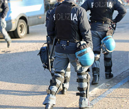 flak: Italian police in riot gear with flak jackets and protective helmets and batons billy