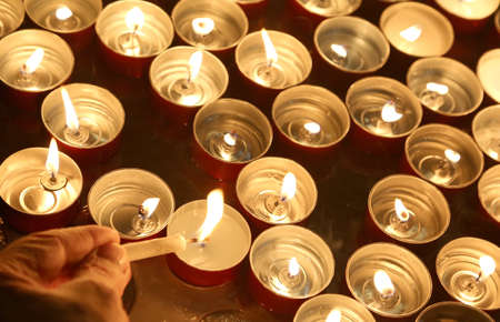 rite: hand of the person who lights a candle during the religious ceremony