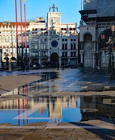 Venice, VE  Italy Piazza San Marco at high tide that is shrinking and the clock tower reflection on the water Stock Photo
