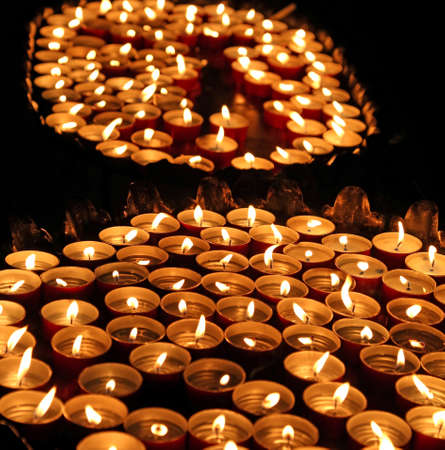 many candles lit with the warm flame during the religious rite