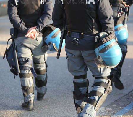 flak: Italian police in riot gear with flak jackets and protective helmets and billy