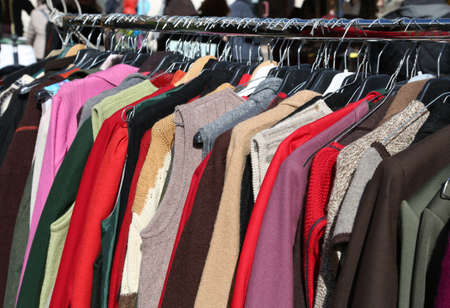 used clothes hung from hangers for sale in flea market