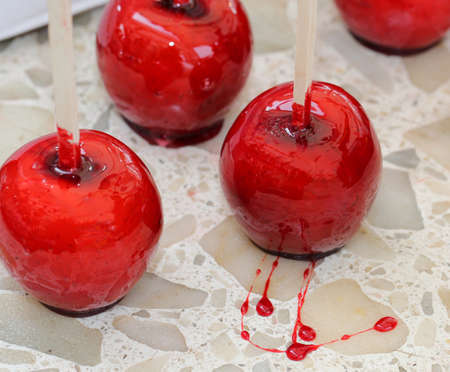 caramelized red apple with wooden stick to eat it