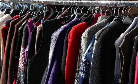 多くの服やセーターの市場の販売のためのハンガーからぶら下がっています。
