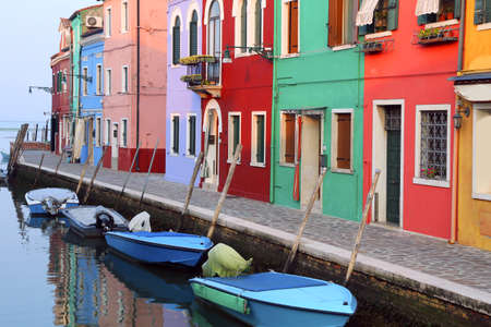 island of Burano and boats in the waterway and colorful houses in Italy near Venice